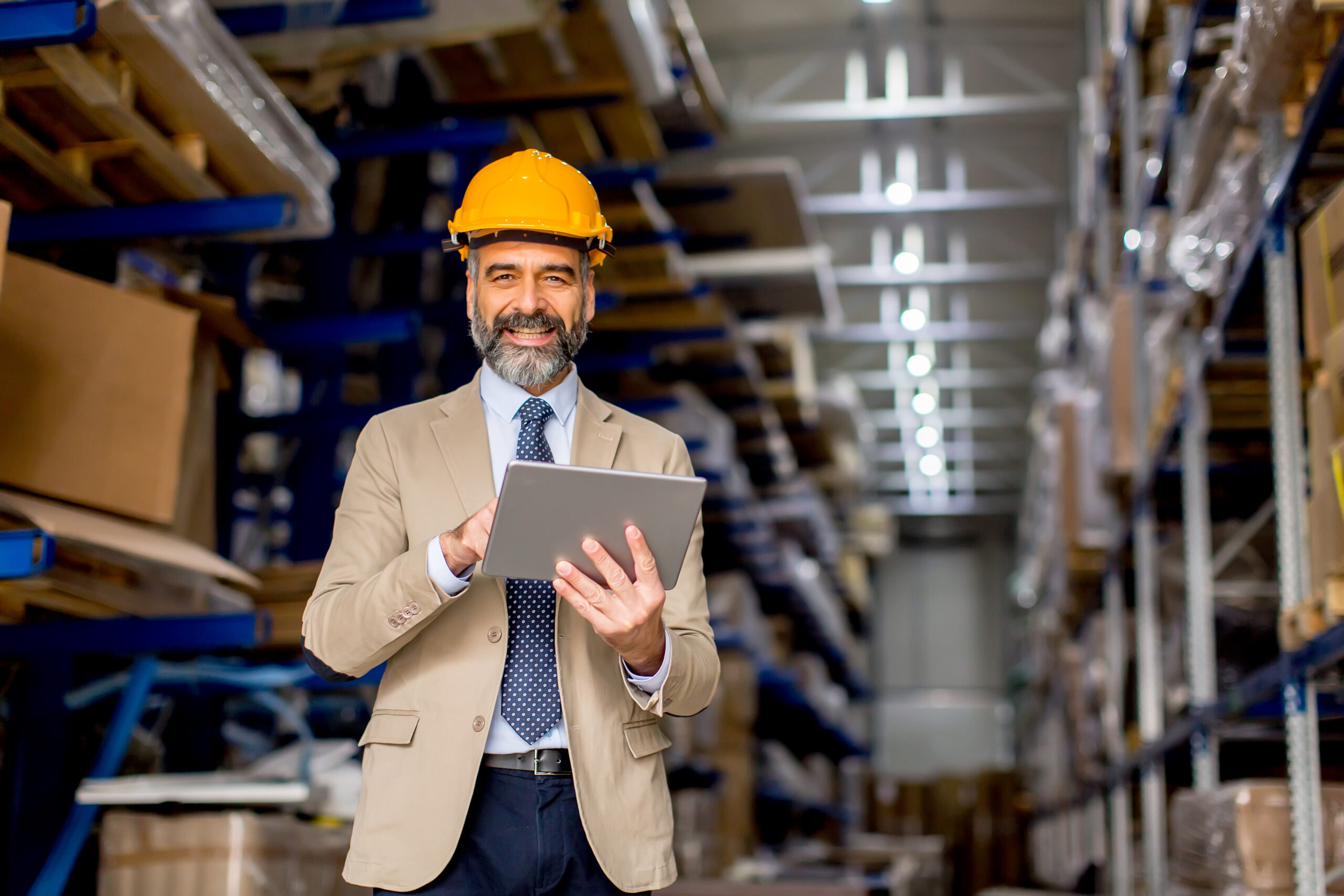 Mature engineer in the warehouse with digital tablet