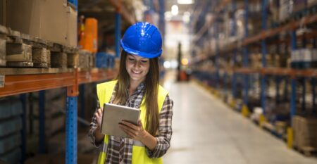 warehouse-female-worker-checking-inventory-on-digital-tablet-in-large-distribution-warehouse-storage-area